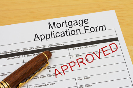 borrowing: Mortgage Application Form with approved stamp and a pen on a wooden desk