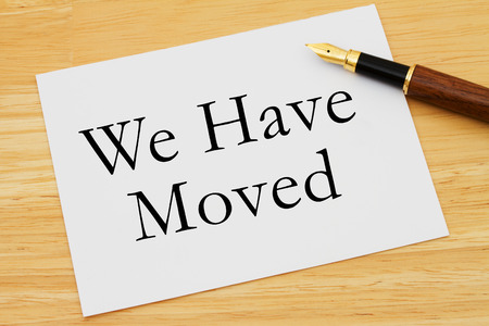 we have moved: We Have Moved Message, A white card with text of  We Have Moved and a fountain pen on a wooden desk
