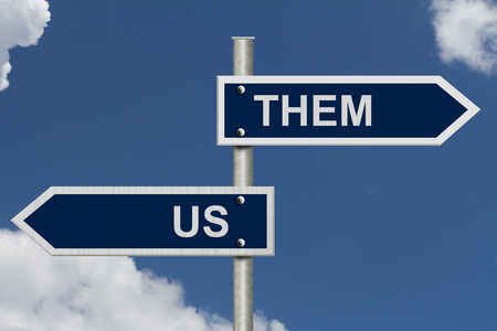 them: Blue street signs with blue sky with words Us and Them, Us versus Them