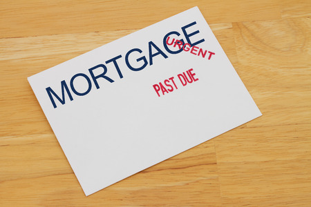 Mortgage Payment envelop with past due and urgent stamps on a wooden desk