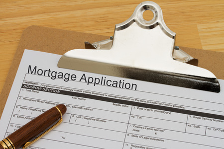 borrowing: Mortgage Application Form on a clipboard with a pen on a wooden desk Stock Photo