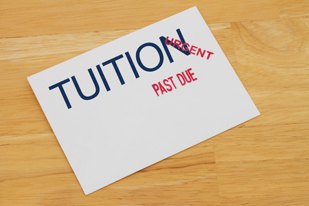 borrowing: Tuition Payment envelop with past due and urgent stamps on a wooden desk Stock Photo