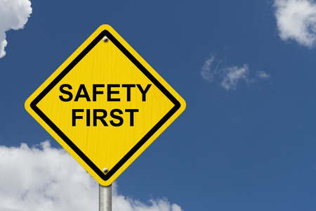 safety first: Safety First Warning Sign, Yellow warning sign with words Safety First Warning with blue sky background Stock Photo