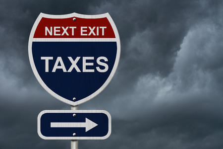 Taxes this way, Blue and Red Interstate Sign with word Taxes and an arrow with stormy sky background photo