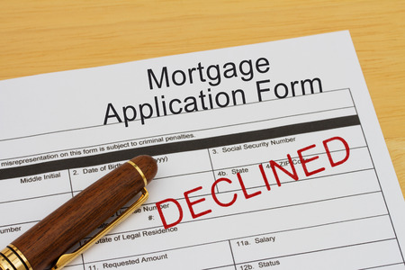 borrowing: Mortgage Application Form with declined stamp and a pen on a wooden desk