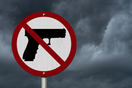 9mm: No Firearms Allowed Sign, An red road sign with handgun icon and not symbol with stormy sky background Stock Photo
