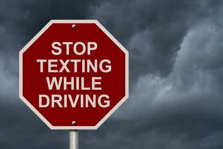 Stop Texting While Driving Sign, Red and White Stop sign with words  photo