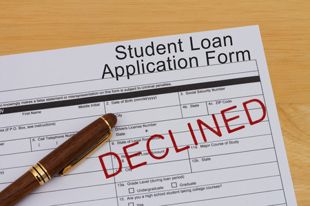 rejected: Student Loan Application Form with a pen and declined stamp on a wooden desk