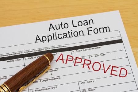 tampon approuv�: Formulaire de demande de pr�t auto avec le timbre approuv� et un stylo sur un bureau en bois Banque d'images