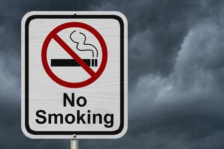 No Smoking Sign, Red and White sign with words No Smoking and cigarette symbol with stormy sky background