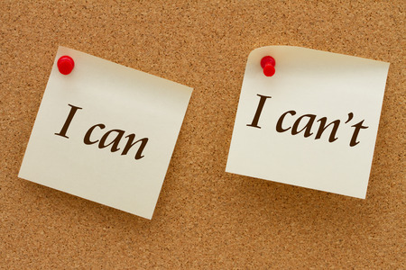 cant: I can versus I cant, Two yellow sticky notes on a cork board with the words I can and I cant Stock Photo