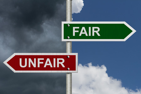 unfair: Red and green street signs with blue and stormy sky with words Fair and Unfair, Fair versus Unfair Stock Photo