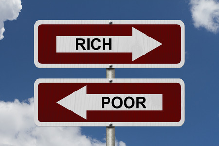 Rich versus Poor, Red and white street signs with words Rich and Poor with sky background photo