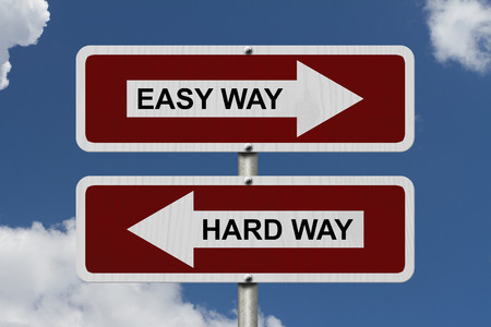 hard way: Hard Way versus Easy Way, Red and white street signs with words Hard Way and Easy Way with sky background Stock Photo