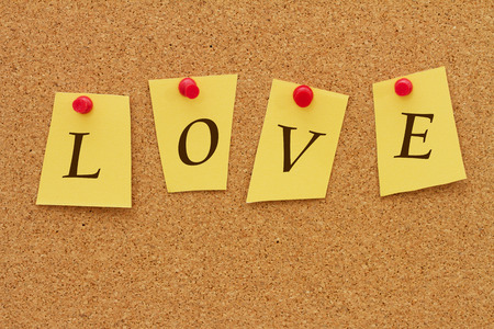 Love, Four yellow notes on a cork board with the word Love 스톡 콘텐츠