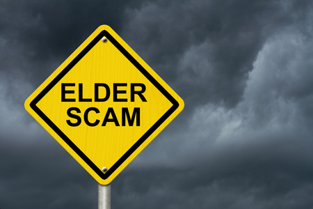 scam: Elder Scam Warning Sign, Yellow warning sign with words Elder Scam with a stormy sky background