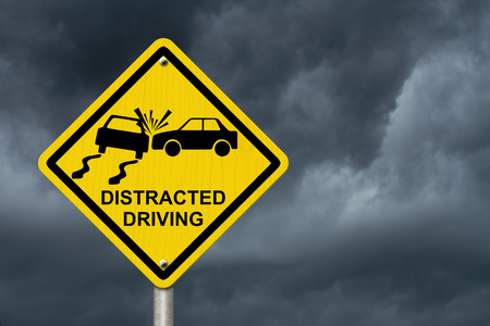 No Distracted Driving Sign, Yellow warning sign with words Distracted Driving and accident icon with stormy sky background