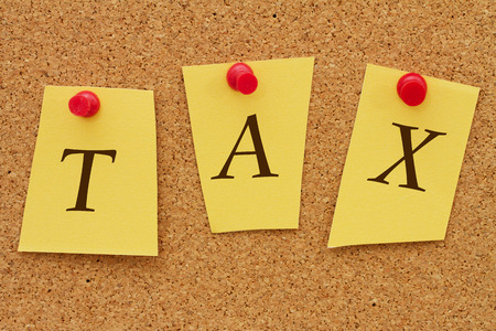 inform information: Taxes, Three yellow notes on a cork board with the word TAX