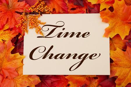 시간 변경 카드, 레드와 오렌지 메이플 리프 배경 위에 단어를 시간 변화에 베이지 색 카드