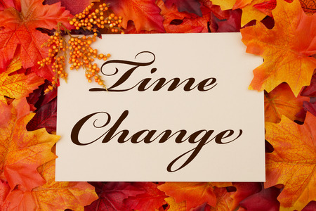 fall time: A Time Change card, A beige card with words Time Change over red and orange maple leaf background Stock Photo