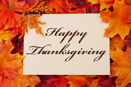 A Happy Thanksgiving card, A beige card with words Happy Thanksgiving over red and orange maple leaf background