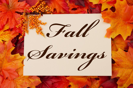 A Fall Savings card, A beige card with words Fall Savings over red and orange maple leaf background photo