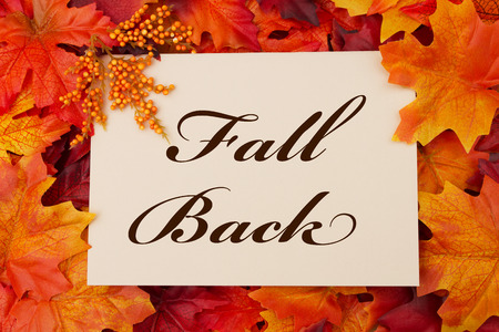 in time: A Fall Back card, A beige card with words Fall Back over red and orange maple leaf background