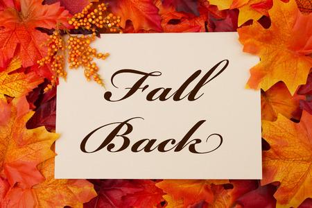 ahorros: Un otoño tarjeta Volver, una tarjeta de color beige con palabras Fall Back sobre fondo rojo y naranja hoja de arce
