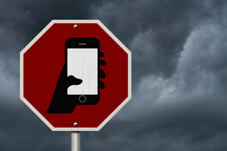 No Texting and Driving Sign, Red Stop sign with symbol of a hand and texting isolated with a stormy sky background