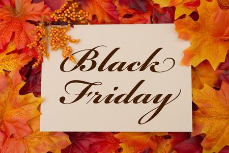 A Black Friday card, A beige card with words Black Friday over red and orange maple leaf background