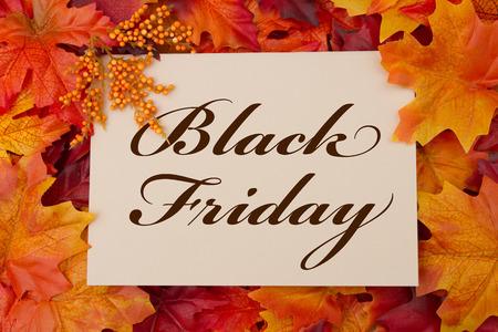 A Black Friday Karte, A beige Karte mit Worten Black Friday auf rot und orange Ahornblatt Hintergrund Standard-Bild - 33986815