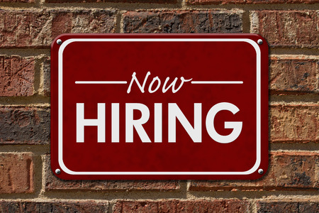Now Hiring Sign,  A red sign with the word Now Hiring with an arrow on a brick wall Stock Photo