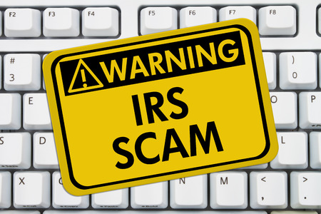 IRS Scam Warning Sign,  A yellow sign with the words IRS Scam on a keyboard 스톡 콘텐츠