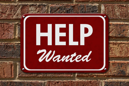 help: Help Wanted Sign,  A red sign with the word Help Wanted with an arrow on a brick wall Stock Photo