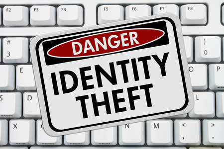 identity theft: Identity Theft Danger Sign,  A red and white sign with the words Identity Theft on a keyboard Stock Photo