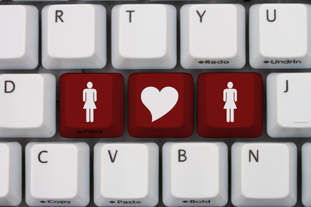 website words: Online Dating, A gray computer keyboard with woman and woman symbol with a heart in red letters Stock Photo
