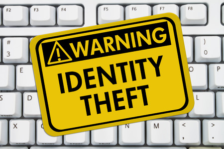 web scam: Identity Theft Warning Sign,  A yellow sign with the words Identity Theft on a keyboard