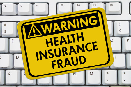web scam: Health Insurance Fraud Warning Sign,  A yellow sign with the words Health Insurance Fraud on a keyboard