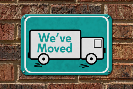 We have Moved Sign,  A teal sign with the word Weve Moved with a truck on a brick wall