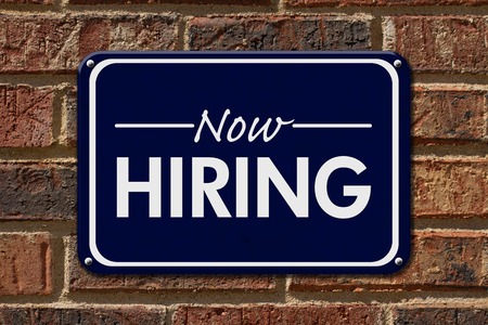 help: Now Hiring Sign,  A blue sign with the word Now Hiring with an arrow on a brick wall