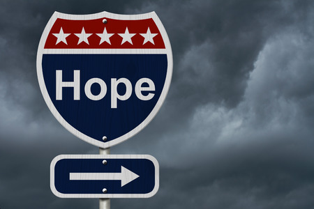 highway sign: Hope Sign, A red, white and blue highway sign with word Hope and an arrow sign with stormy sky background Stock Photo
