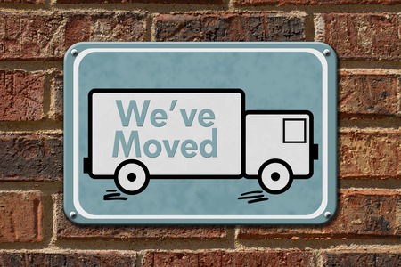 moved: We have Moved Sign,  A blue sign with the word Weve Moved with a truck on a brick wall Stock Photo