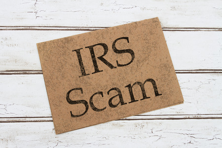 A IRS Scam Warning Card, A brown card with words IRS SCAM over a distressed wood background Stock Photo