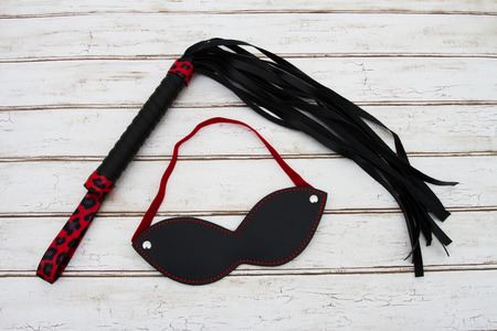 erotic fantasy: BDSM Toy, A black and red BDSM toy, a whip and mask over a distressed wood background