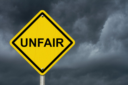 unfair: Caution sign with word Unfair with stormy sky background Stock Photo