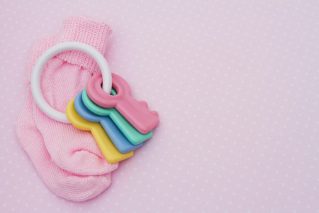 copyspace: Pink Baby Background, Pink baby socks with soother in pink and white polka dot background with copy-space for your message Stock Photo