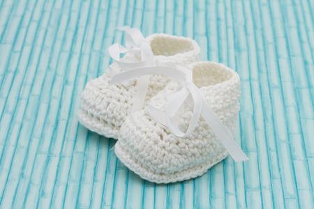 Retro botines bebé, blanco botines del bebé en un fondo de madera del grunge