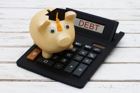 education loan: Calculating your student loan debt, A golden piggy bank with a grad hat on a calculator with word Debt over a distressed wood background Stock Photo