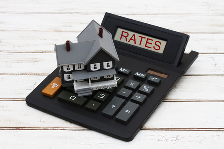 mortgage rates: Calculating your  interest rates, A gray model house on a calculator with word Rates over a distressed wood background
