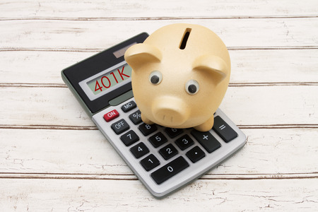retirement savings: Retirement Savings, A golden piggy bank on a calculator with word 401K over a distressed wood background Stock Photo